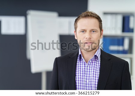 Serious concerned young businessman staring at the camera with a look of consternation as he stands in the office, head and shoulders view - stock photo
