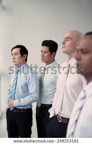 Serious confident business people looking through the window - stock photo