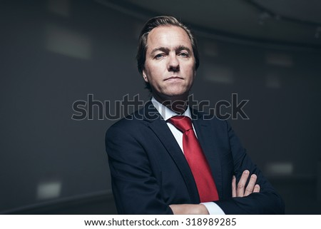 Serious confident businessman with red tie in room. Looking in camera. - stock photo