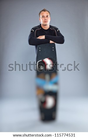 Serious confident man with short hair wearing wetsuit. Holding kiteboard. Kite surfer. Studio shot. Isolated on grey background. - stock photo