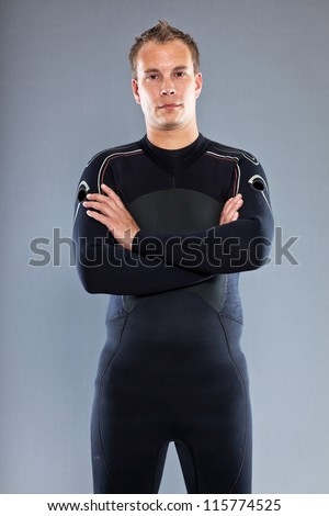 Serious confident man with short hair wearing wetsuit. Kite surfer. Studio shot. Isolated on grey background. - stock photo