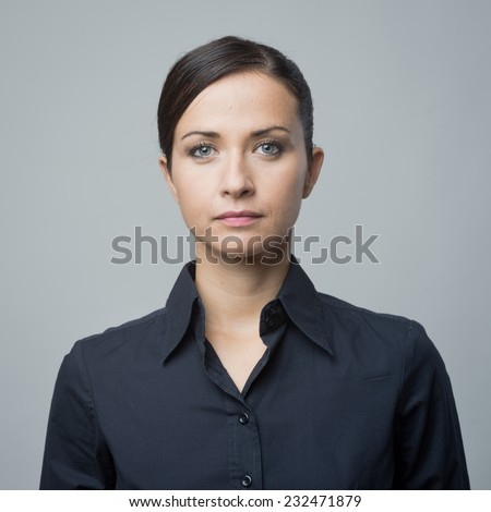 Serious confident woman in blue shirt staring at camera. - stock photo