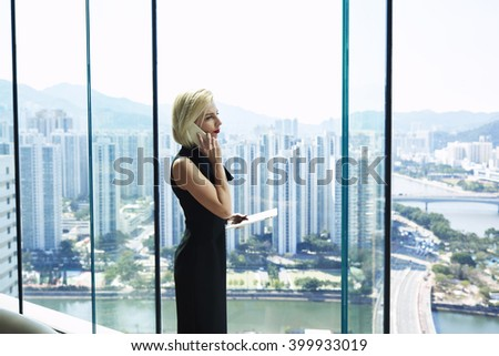 Serious confident woman lawyer is holding digital tablet and calling via cell telephone to her client to further refine your certain questions, while is standing near office window with copy space - stock photo