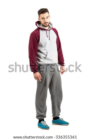 Serious confident young man in casual sportswear looking at camera. Full body length portrait isolated over white studio background.  - stock photo