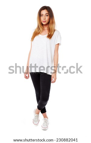 Serious confident young woman with long blond hair dressed in casual wear standing with her feet crossed looking at the camera, full body over white - stock photo
