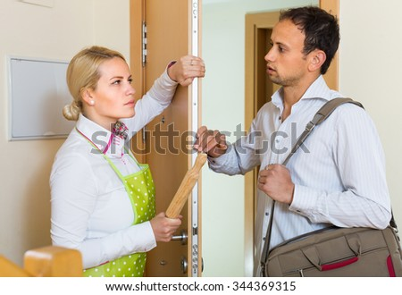 Serious conflict between angry wife and husband at the door - stock photo