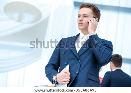 Serious conversation. Confident businessman talking on a cell phone and holding a tablet in her hand looking to the side while his colleagues talking in the background. - stock photo