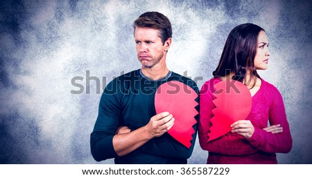 Serious couple holding cracked heart shape against grey background - stock photo