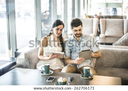 Serious Couple love sit on sofa couch look at tablet computer Woman show screen with image or site Family, technology internet happiness concept concentrated couple with smartphones at free wi fi cafe - stock photo