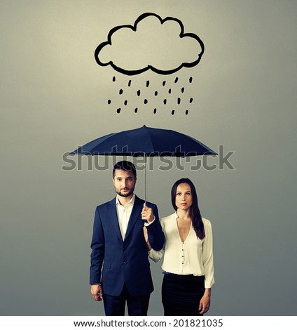 serious couple with black umbrella standing under drawing storm cloud. photo over grey background - stock photo
