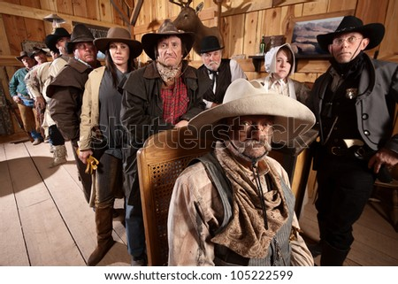 Serious customers in classic old American west saloon - stock photo