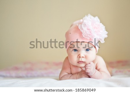 Serious cute baby in hat with flower  - stock photo