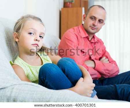 Serious dad and offended european little girl quarrelling indoors. focus on girl