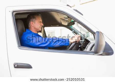 Serious delivery man driving his van outside the warehouse - stock photo