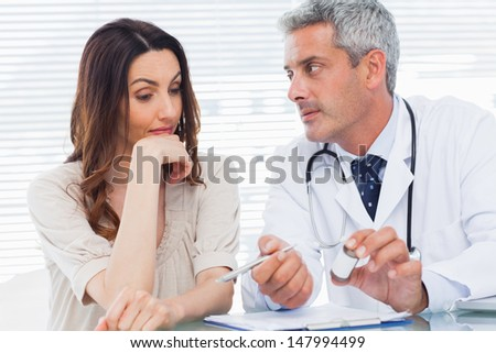 Serious doctor listening to his patient in medical office - stock photo