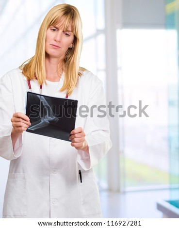 serious doctor looking at an x-ray against an abstract background - stock photo