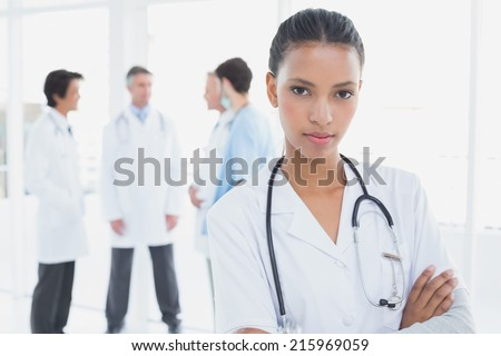 Serious doctor looking at camera with colleagues behind her - stock photo
