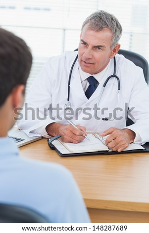 Serious doctor prescribing drug to his patient in bright surgery