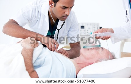 Serious doctor resuscitating a patient in a hospital - stock photo