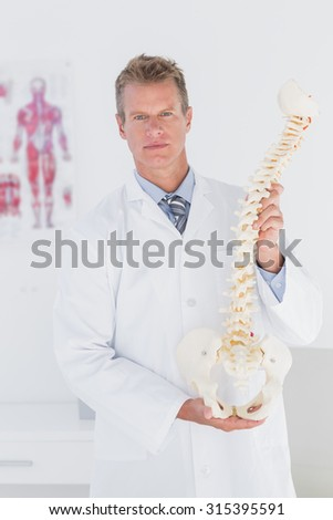 Serious doctor showing anatomical spine in medical office - stock photo