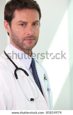 Serious doctor with stethoscope - stock photo
