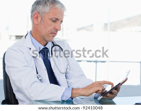 Serious doctor working with a tablet computer in his office - stock photo