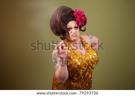 Serious drag queen smoking cigarette on green background