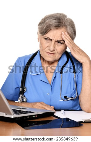Serious elderly woman doctor sitting at table with computer, x-ray and making notes