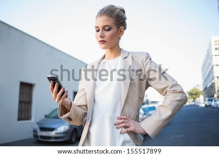 Serious elegant businesswoman looking at her smartphone outdoors on urban background