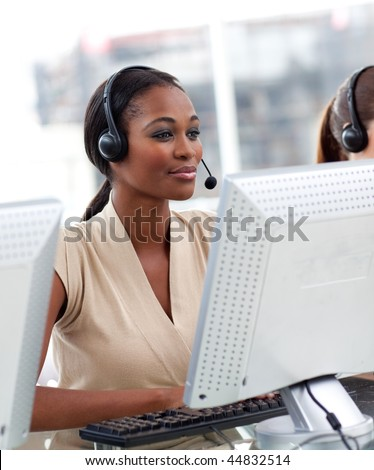 Serious ethnic businesswoman with headset on working in a call center - stock photo