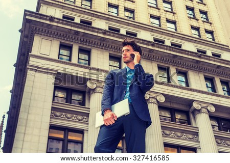 Serious European Businessman traveling, working in New York. Dressing in blue suit, carrying laptop computer, a young guy with beard standing on street with high buildings, talking on mobile phone.  - stock photo