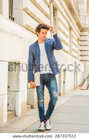 Serious European college student studying in New York. Wearing blue blazer, jeans, sneakers, holding a laptop computer, hand touching hair, a young guy walking on campus, thinking. Instagram effect.