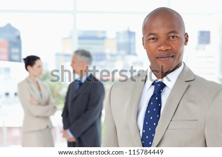 Serious executive in a suit standing upright while his team is behind him - stock photo