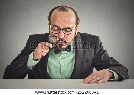 Serious executive man director sitting at desk skeptically looking through magnifying glass at table isolated wall office background. Face expression. Application offer evaluation process concept