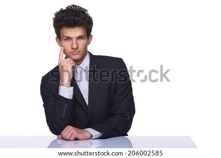 Serious fashionable business man sitting on table with hand on cheek, over white background