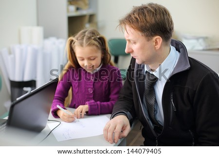 Serious father looks at his little daughter drawing picture on his papers. They choose apartment. Focus on man. - stock photo