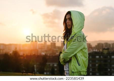Serious female athlete crossing arms towards sunrise or sunset over city skyline for sport motivation and fitness lifestyle concept. - stock photo