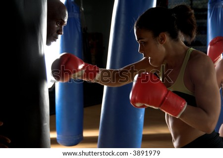 Serious female boxer throwing a right cross at the heavy bag being held by her trainer while he looks around the bag - stock photo
