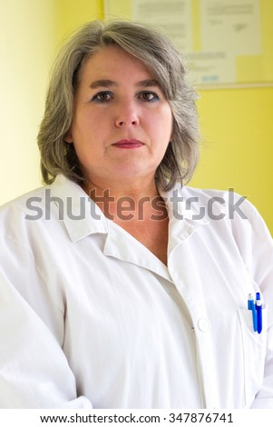 Serious female doctor portrait, in consulting room   - stock photo