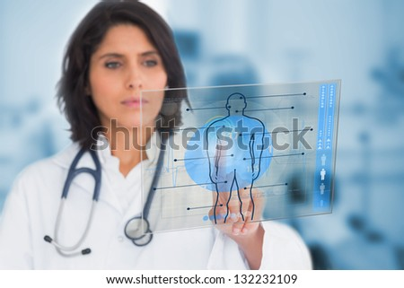 Serious female doctor touching a touchscreen on hospital - stock photo