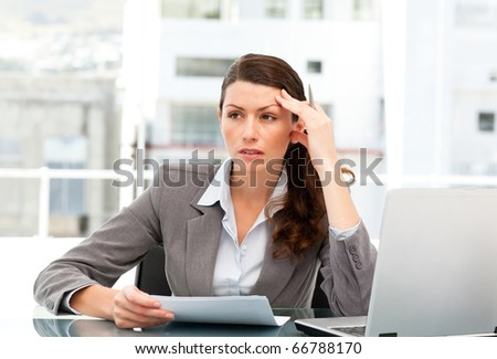 Serious female executive finding ideas while working at her desk with laptop - stock photo