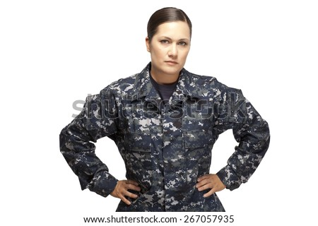 Serious female in navy uniform posing with hands on hips against white background - stock photo