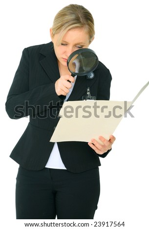 serious female investigator look at folder through loupe - stock photo
