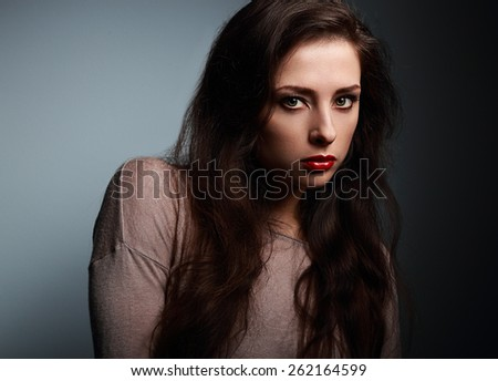 Serious female model with unusual artistic look on dark background. Closeup - stock photo