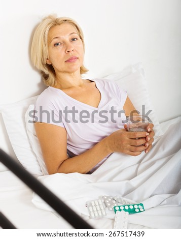Serious female pensioner taking medicine before falling asleep - stock photo
