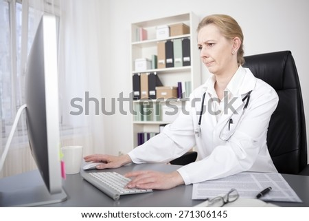 Serious Female Physician Sitting at her Office Accessing Medical Information Through Online Using her Desktop Computer. - stock photo