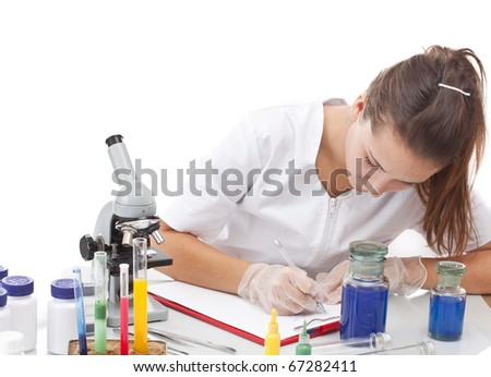 Serious female scientist writing on her clipboard in front of a microscope, focus on the hand