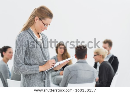 Serious female therapist writing notes with group therapy in session in background - stock photo