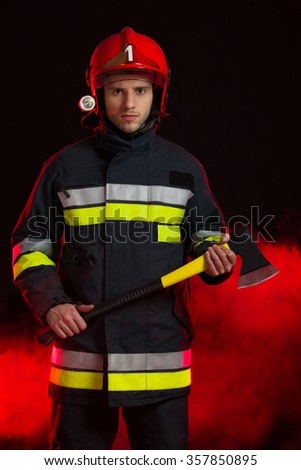 Serious fireman in red helmet holding an axe and standing in smoke. Three quarter length studio shot on black background. - stock photo
