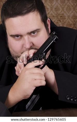 Serious gangster holding handgun, close up. - stock photo